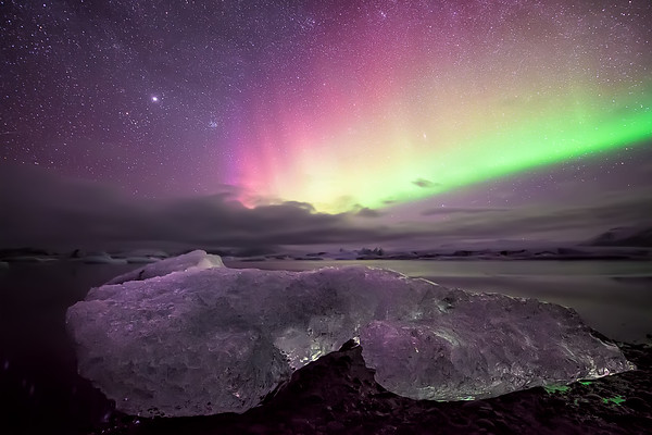 Photograph: Aurora Rainbow - Bright Aurora Borealis over some ice on the edge of the Jökulsárlón lagoon.