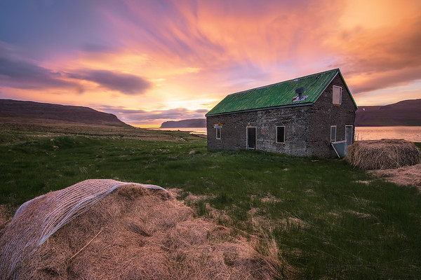 Photograph: Fishing at Midnight - A stone fishing hut in the Westfjords at midnight during the Midnight Sun.