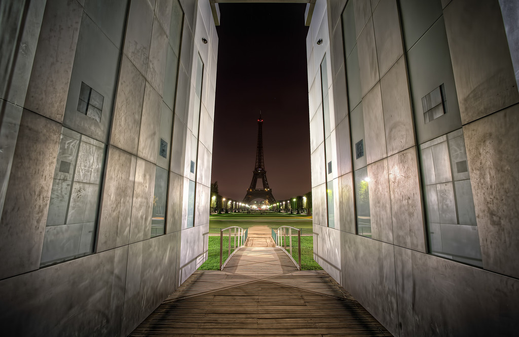 Photograph: Darkness and Peace - The Eiffel Tower at night, seen though the Peace Wall.