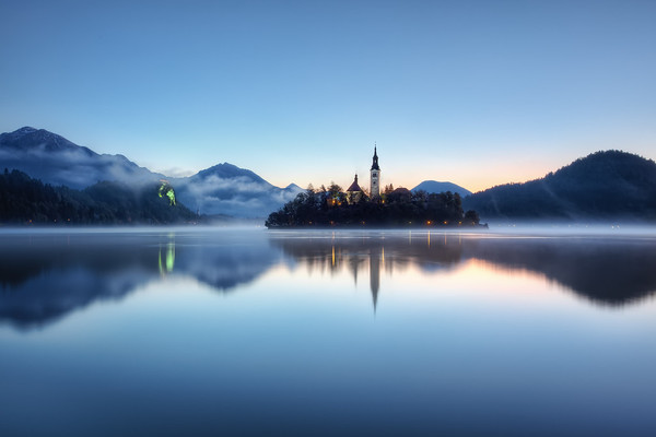 Photograph: Feeling Blue - A very blue sunrise over Lake Bled in Slovenia. Bled Island and Church sit in the middle of this lake scene.