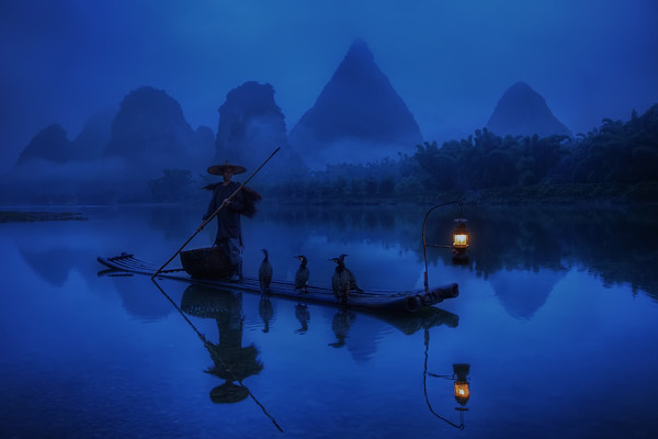 Photograph: Cormorant Fisherman - A cormorant fisherman starting his dawn shift on the Lijiang River in Yangshuo, Guilin.