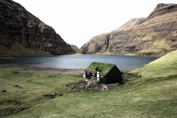Photograph: Solitary Saksun - A lone turf-roofed house stands surrounded by mountains in the village of Saksun.