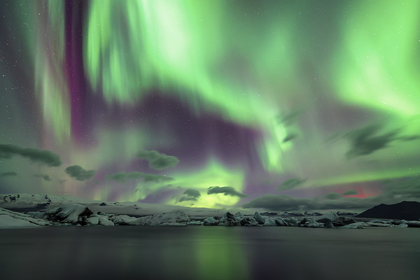 Photograph: Fire In The Sky - Aurora borealis above Jökulsárlón ice lagoon in Southern Iceland. The glow of the volcanic eruption at Holuhraun is reflected off the clouds.