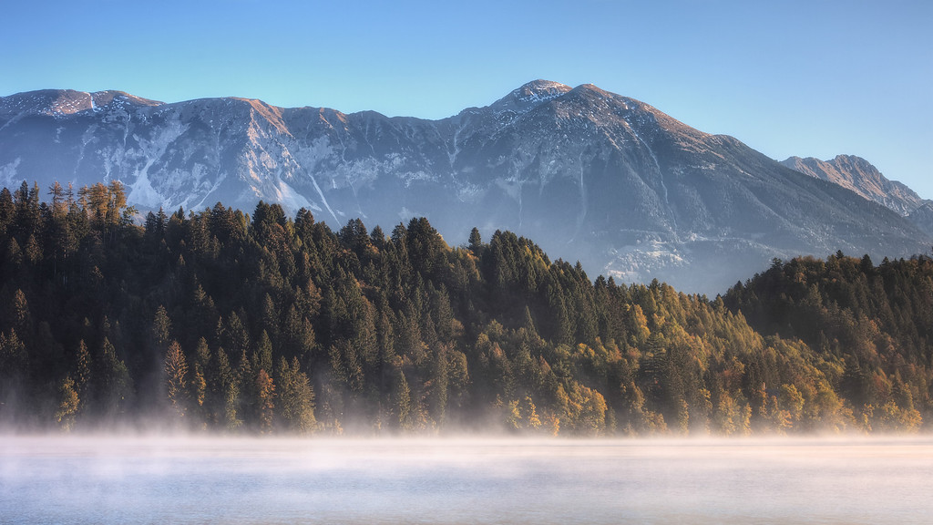 Photograph: Misty Morning Alps - Morning sun hitting the Julian Alps by Lake Bled in Slovenia.