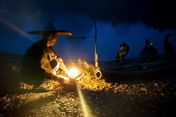 Photograph: The Fisherman and The Lamp - A cormorant fisherman in Yangshuo lights his lamp before setting off down the river.