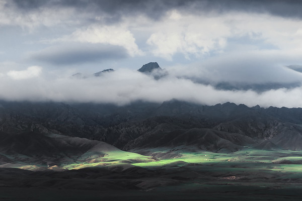 Photograph: Mountains of Mongolia - The sun peaks through the low lying clouds around the Gurvan Saikhan Mountains in the Gobi region of Southern Mongolia.