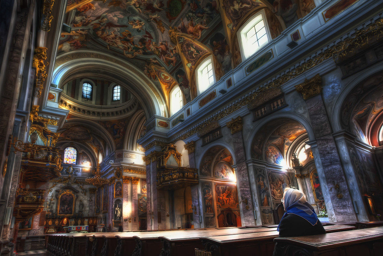 HDR shot of a lone woman praying in the Cathedral of St. Nicholas in Ljubljana, Slovenia.