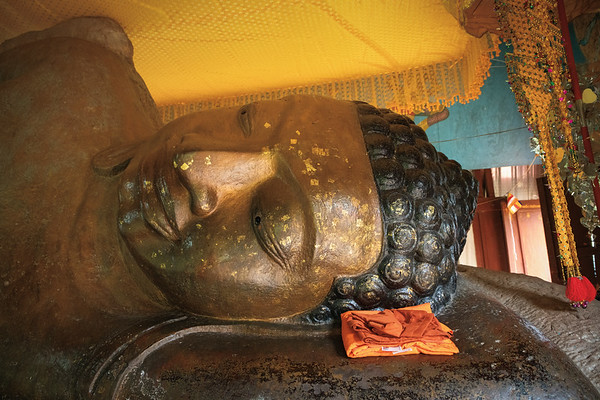 Closeup of the face of the reclining Buddha and a neatly wrapped shawl