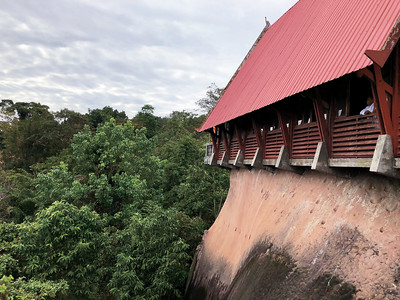 Preah Ang Thom Pagoda  and its red roof built to house and surround the reclining Buddha carved into the mountain, seen from the giant stone staircase outside overlooking the jungle