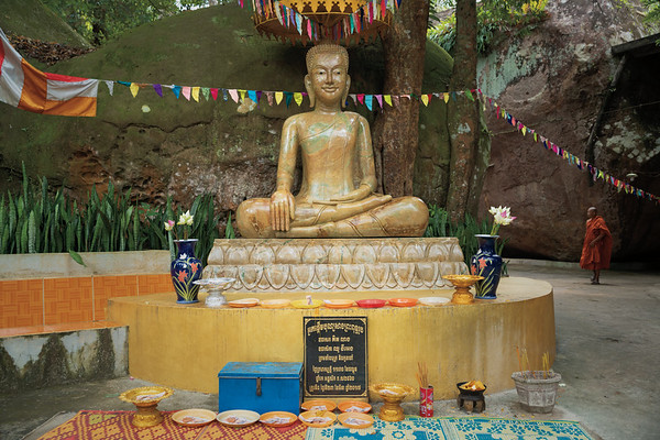 Golden Buddha and many full offering plates in the outer courtyard to the temple with a monk passing by on daily rituals