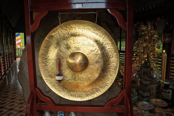 Giant gong and seated Buddha with offering plates inside the pagoda
