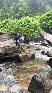 Me setting up on a sandstone outcropping in the middle of the rushing river getting ready to shoot pictures of Kulen Mountain Waterfall
