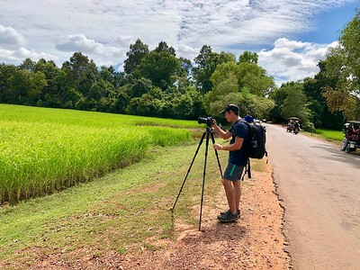 Me hard at work along Cambodian Route 67 taking photos of a glorious Angkorian rice field in full bloom (photo by Boren)