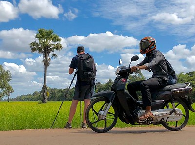 Me along Cambodian Route 67 taking photos of a glorious Angkorian rice field in full bloom and to show just how close traffic passed by every few seconds (photo by Boren)