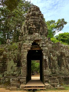 Eastern gate and entrance to Banteay Kdei with the smiling face of Jayavarman VII, and above featuring the gateway's laterite walls and ornate aspara reliefs backdropped by the canopy of the forest