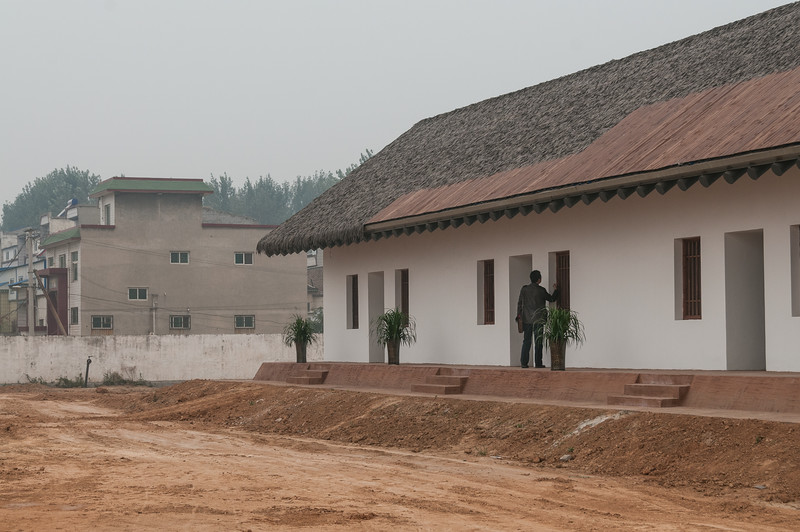 A tourist enters reconstruced Building 8 of the palace site at Yanshi Shangcheng (Tazhuang, Yanshi, Henan, CN - 10/29/13, 10:12:18 AM)