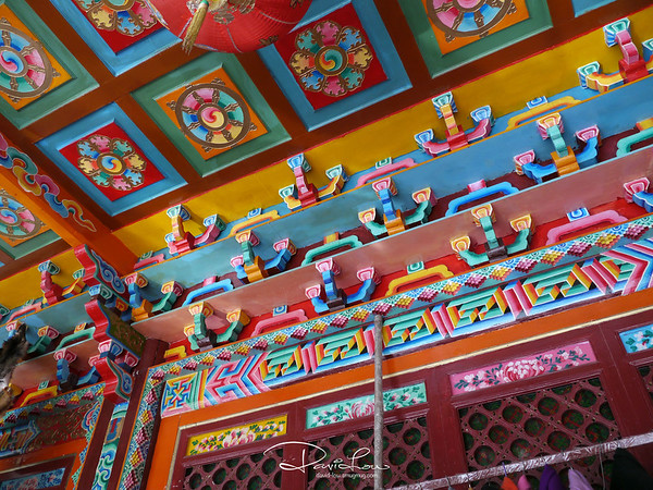 A typical Tibetan interior - mostly arty with fanciful colourful architraves and carvings.