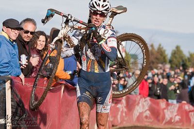 Hudz-Subaru elite rider Nicole Duke of Boulder, CO (#19) runs with her bike after getting caught in a collision on a muddy section of the USA Cycling Cyclo-Cross Nationals in Bend Oregon on December 12, 2010.  Nicole finished 6th overall.