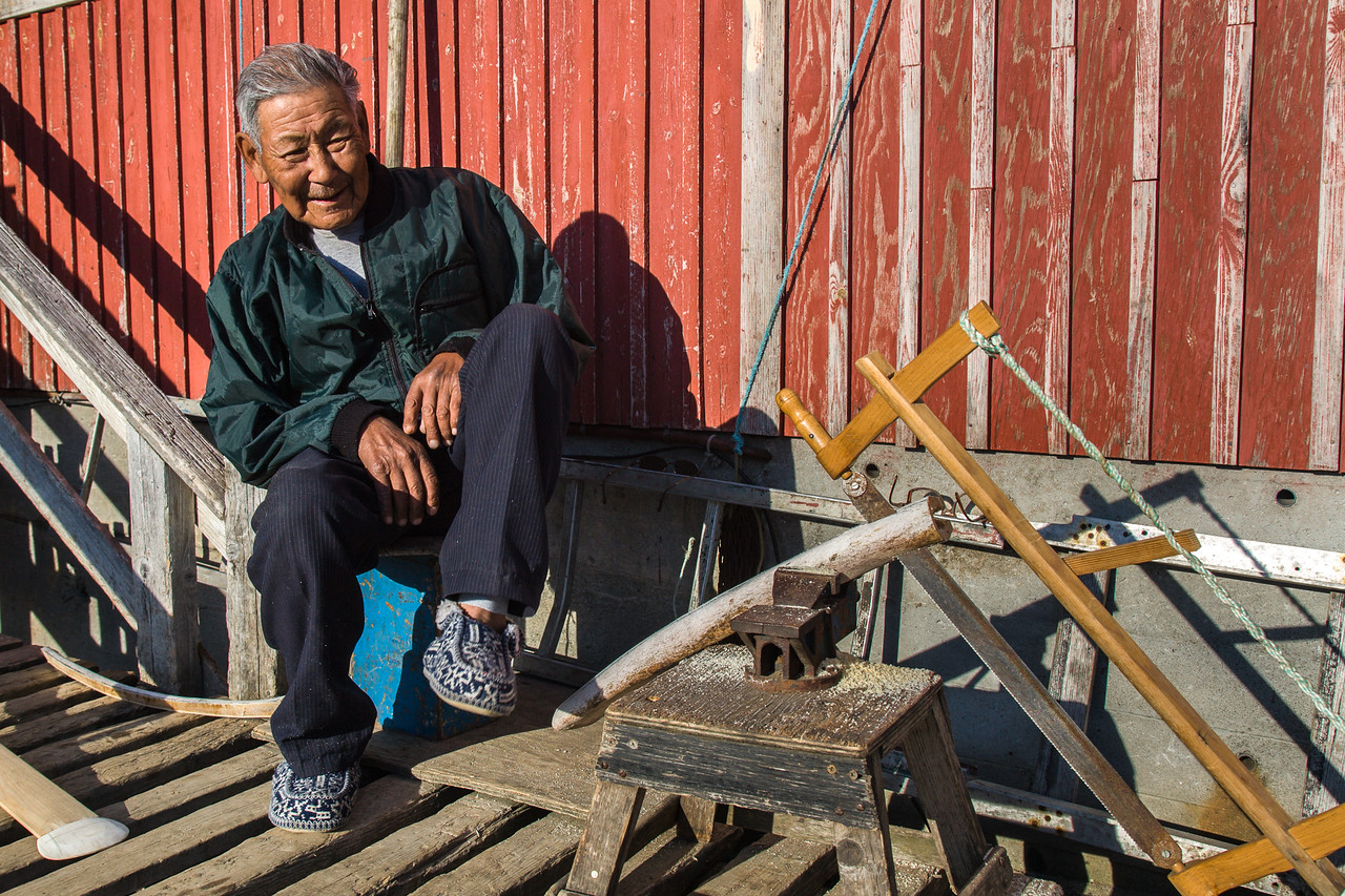 An elderly Inuit man sawing whale bone for a kayak paddle.