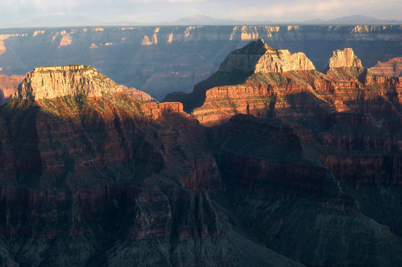 Late evening shadow across Bright Angel Canyon - to the sunlit peaks of Deva Temple, Brahma Temple, and Zoroaster Temple - to the distal south rim (which is about 1,000 ft./305 m lower, than the north rim) of Grand Canyon.