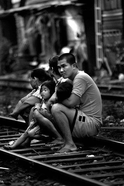 A family sits on the tracks and relaxes in the evening outside their small shack in a ghetto in central Bangkok, Thailand.