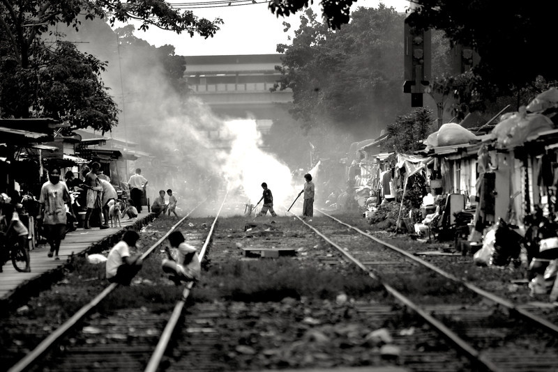 With no government services available, residents burn their trash alongside the railroad tracks in this slum in central Bangkok.