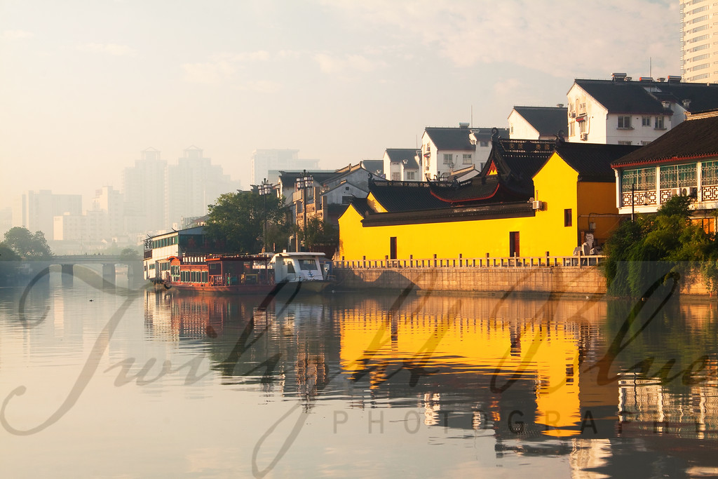 Suzhou Canal <br /> Suzhou, Jiangsu, China<br /> <br /> The ancient city of Suzhou is made up of a network of canals and waterways and is surrounded by a moat with eight gates, originally used as a line of defense against invaders. Now a city of old versus new, skyscrapers serve as a backdrop for the bright colors of the historic buildings along the Yangtze River.