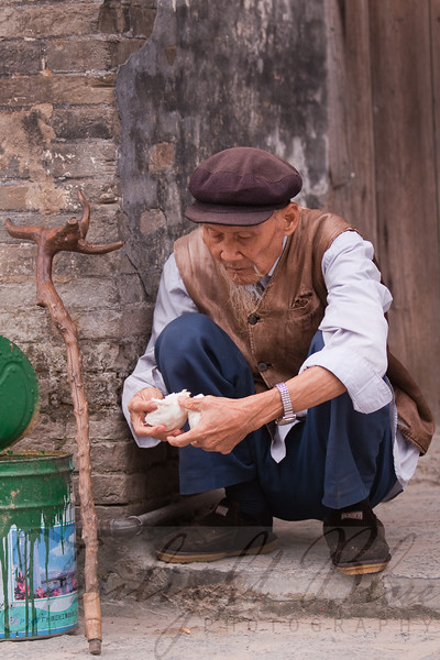 Old Man Eating Fruit<br /> Old Town<br /> Xingpin, Guangxi, China<br /> <br /> The old man is eating his fruit in a casual squatting position, used for relaxation and going to the bathroom. His cane, clothes and beard represent Chinese traditional attire. The fruit he is eating is called pumello, a common food of the Guangxi Region.