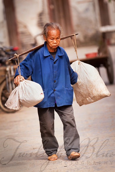 Traditional Worker<br /> Old Town<br /> Xingpin, Guangxi, China<br /> <br /> A traditional way of life is still prevalent in modern China. Here we see a  worker carrying rice across her shoulders as she walks down one of the oldest streets in China.