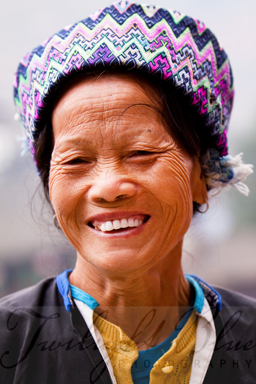 Zhuang Minority Porter<br /> Ping'an Village, Guangxi, China<br /> <br /> When you arrive at the base of the village of Ping'an, you are greeted by a band of women and an occasional man with large woven baskets fastened to their backs. These people, in their colorful clothes and towel like head pieces, are porters ready to carry your gear up the very steep stairway leading to the main village.<br /> <br /> This woman is one of the eight porters we utilized on our visit. As a general rule, we found dental hygiene to be very poor throughout China. However, in this village a number of the women had veneers.