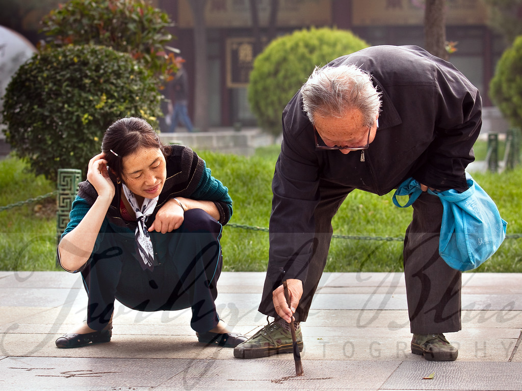 Learning from the Master<br /> Wild Goose Pagoda Park<br /> Xian, Shanxi, China<br /> <br /> Chinese Calligraphy is an art form passed on from generation to generation. Each character is a symbol made of many strokes. Certain stroke orders were recommended to ensure speed, accuracy, and legibility in composition. <br /> <br /> A common scene in the parks of China is to see people practicing their calligraphy using water and an over-sized brush tracing symbols carved into the walkways.