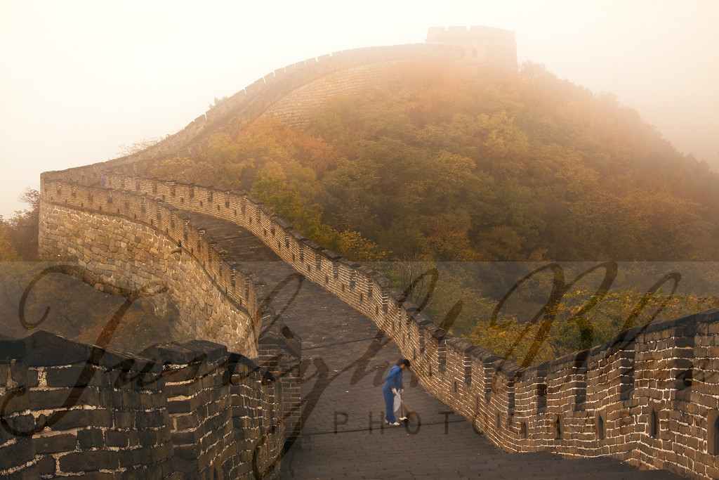 The Great Clean-up<br /> Great Wall of China<br /> Mutianyu, Huairou District, China<br /> <br /> The Great Wall of China is one of the Seven Wonders of the World and a huge attraction for thousands of visitors each day. In order to beat the crowds, our group hopped onto the very first gondola to the top of the Great Wall finding a lone street cleaner working on this very hazy morning. Minutes later, throngs of people descended onto the Wall ending our very private moment at a very public place.