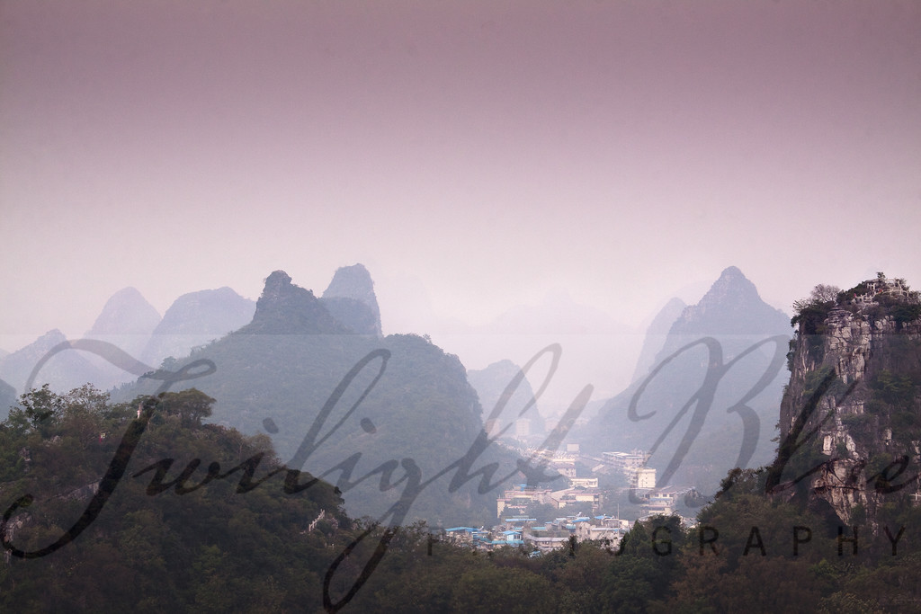 Morning Over Guilin<br /> Guilin, Guangxi, China<br /> <br /> Our predawn hike to the top of the Folded Brocade Mountain in the Pinnacle Mountains proved to be as memorable as it was photogenic.  To the east, we watched the moon pass over the city of Guilin and to the west; we watched the sun rise over the Li River.<br /> <br /> Notice the solitary woman in the image as she performs her morning ritual on a mountain top over the city of Guilin.