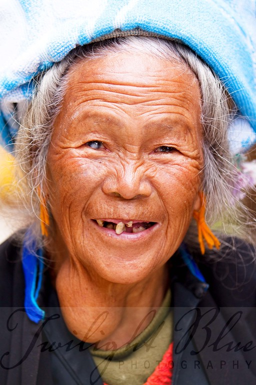 Zhuang Minority Woman<br /> Ping'an Village, Guangxi, China<br /> <br /> This Zhuang Minority elder woman is intrigued by the visitors in her village. The sparkle in her eye and the smile on her face make her a fine ambassador.<br /> <br /> Ninety-six percent of the Chinese population is made of the Han ethnic group. The Zhuang Minority is the largest of the 55 minority groups acknowledged in China.