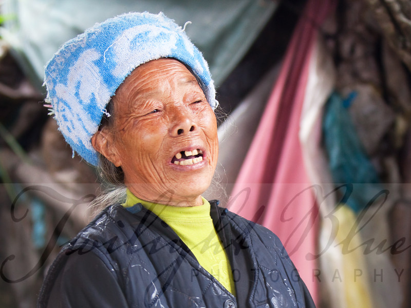 Woman Singing <br /> Ping'an Village, Guangxi, China<br /> <br /> While on the top of the mountain high above Ping'an Village, we met an elderly Zhuang woman. Her home was a make-shift hut along side the new tourist pavilion over looking the terraced rice paddies.<br /> <br /> The years of hard labor in the rice fields were quite evident by her rough hands, but her spirit remained bright. As a gift to her guests she sang a beautiful song of joy and happiness in the morning air.