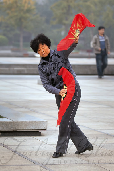 Morning Exercise with Red Fans <br /> Wild Goose Pagoda Park<br /> Xian, Shanxi, China<br /> <br /> Morning exercise is a community event in public places. Everywhere we traveled, groups of people would gather for an hour to do Tai Chi.<br /> <br /> This lovely lady allowed me to photograph her as she went through her morning repertoire. Here she is using two red fans in a graceful display of artistry.