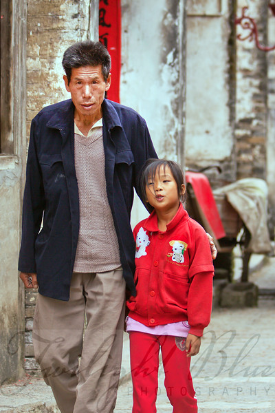Afternoon Stroll<br /> Old Town<br /> Xingpin, Guangxi, China<br /> <br /> School children receive a two hour lunch break each day. This is to allow enough time for the child to walk to and from home to eat. This young girl is telling her father about her busy morning.