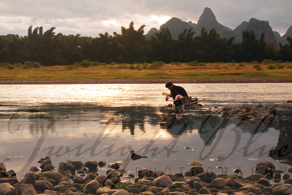 Laundry at Sunrise<br /> Li River<br /> Yangshou, Guangxi, China<br /> <br /> Modern conveniences are not available to everyone in China. Here we see a woman washing her clothes on the rocks in the Li River at sunrise.