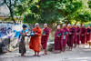 Monks line up for daily meal in a small village on the way to Kampalet