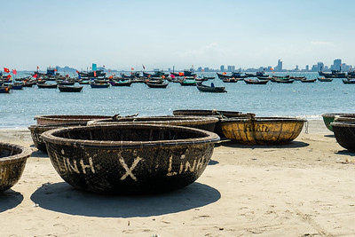 Traditional circular fishing boats sit on the beach in Da Nang.