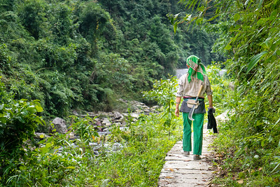 A Hmong woman with a machete strapped to her back follows a trail in Ha Giang province