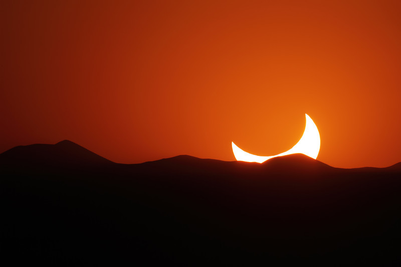 May 20, 2012 - Annular eclipse from El Paso, Texas.  The Sun is sinking below the distant mountains, still eclipsed<br /> <br /> Camera: Canon 7D<br /> Lens: Takahashi FSQ-106ED<br /> Tripod: Quickset HD video tripod<br /> Exposure: ISO 100, f5 @ 1/5000 second<br /> <br /> Location: El Paso, Texas
