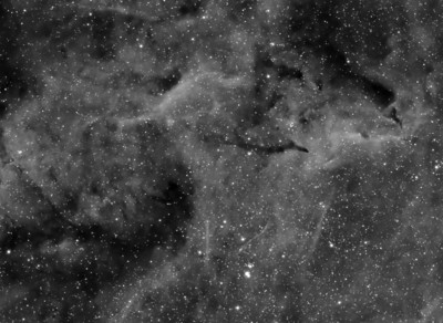 This images is a crop of  the previous image showing Barnard 146 and some interesting filaments.    Date: 9/21/13,  9/23/13  Telescope: Takahashi FSQ-106ED with CAA Mount: Astro-Physics Mach1GTO Guider: Meade DSI Pro through Astrodon MMOAG CCD: Finger Lakes Instruments ML11002 CCD, with 65mm shutter Fiter Wheel: Finger Lakes Instruments CFW-2-7 Filters: Astrodon 3nm Hydrogen Alpha Exposure: 10 x 1800 sec (5 hours)  Software: MaximDL, Registar, Photoshop CS3 with Carboni & GXT Location: Light polluted back yard in El Paso, Texas  Polar Alignment: PoleAlignMax