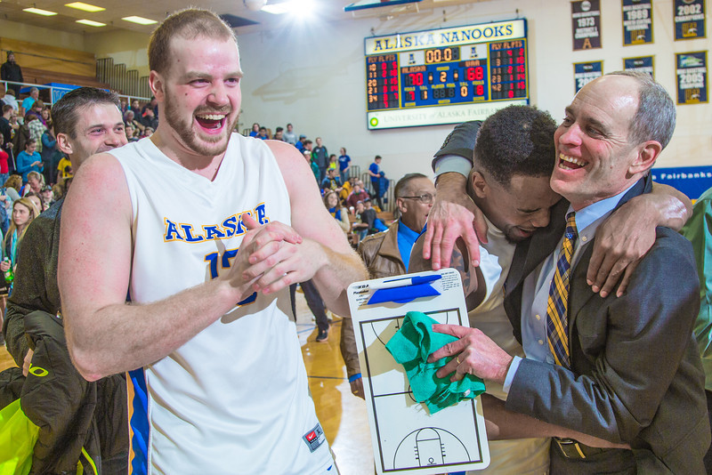 "Men's basketball coach Mick Durham gets a hug from senior guard Ronnie Baker near mid court moments after the Nanooks beat UAA in a thrilling come-from-behind battle on Senior Night in the Patty Gym. Fellow senior Dallen Bills at left, and fans shared in the celebration.  <div class=""ss-paypal-button"">Filename: ATH-14-4097-92.jpg</div><div class=""ss-paypal-button-end"" style=""""></div>"