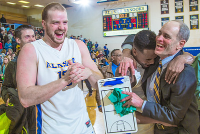 Men's basketball coach Mick Durham gets a hug from senior guard Ronnie Baker near mid court moments after the Nanooks beat UAA in a thrilling come-from-behind battle on Senior Night in the Patty Gym. Fellow senior Dallen Bills at left, and fans shared in the celebration.  Filename: ATH-14-4097-92.jpg