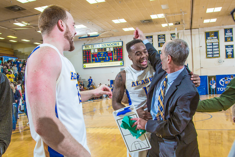 """Men's basketball coach Mick Durham gets a hug from senior guard Ronnie Baker near mid court moments after the Nanooks beat UAA in a thrilling come-from-behind battle on Senior Night in the Patty Gym. Fellow senior Dallen Bills at left, and fans shared in the celebration.  <div class=""""ss-paypal-button"""">Filename: ATH-14-4097-94.jpg</div><div class=""""ss-paypal-button-end"""" style=""""""""></div>"""
