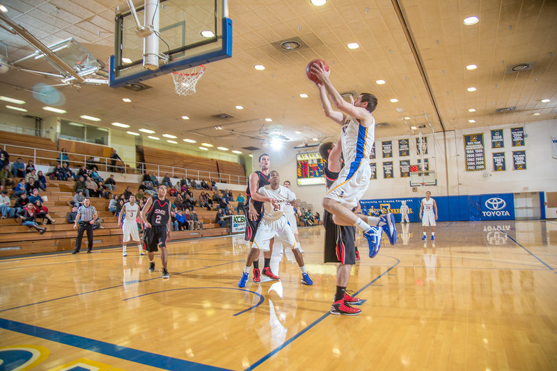 """Junior forward Stefan Tica avoids a charge and banks in a two-pointer during the second half of the Nanooks' 81-58 win over Saint Martin's Jan. 10 in the Patty Center.  <div class=""""ss-paypal-button"""">Filename: ATH-13-3695-67.jpg</div><div class=""""ss-paypal-button-end"""" style=""""""""></div>"""