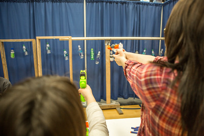 Fans get a chance to shoot nerf guns during breaks in the action on the first day of the 2015 NCAA Rifle Championships in the Patty Center.  Filename: ATH-15-4485-010.jpg