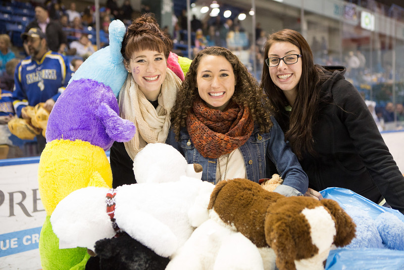 """Student athletes collect plush toys on the ice during the 3rd Annual Teddy Bear Toss at a hockey game in Carlson Center. The Student-Athlete Advisory Committee sponsored the event that collects toys for families during the holiday season.  <div class=""""ss-paypal-button"""">Filename: ATH-13-4011-47.jpg</div><div class=""""ss-paypal-button-end"""" style=""""""""></div>"""