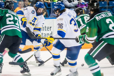 Cody Kunyk, 37, looks to clear the puck to teammate Colton Beck, 36, during the Nanooks' 2-1 win over North Dakota in the Carlson Center.  Filename: ATH-12-3601-11.jpg